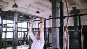 Pulls up on bar in gym. Reverse pull-ups to be fit. Best exercises in the gym. Strong middle-aged man pulls up on bar in gym and wears lift and grip gear stock footage