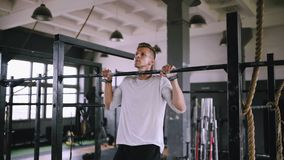 Pulls up on bar in gym. Useful exercises in the gym. Strong middle-aged man pulls up on bar in gym and stayed up, static load on muscles. Strengthening the stock video