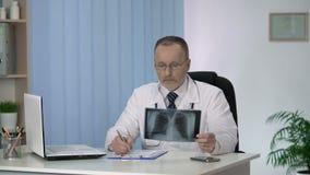 Pulmonologist que examina e que descreve a varredura paciente do raio X dos pulmões antes da cirurgia vídeos de arquivo