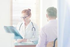 Pulmonologist regardant l'image de rayon X images stock