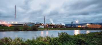 Pulp mill on the banks of the river. Image pulp mill for the production of paper, smoke from the chimneys. Paper production harms the environment, emission of stock photo