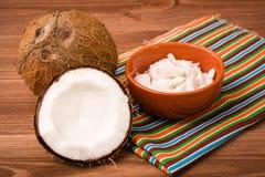 Pulpa del coco en un cuenco y cocos en una tabla de madera Fotografía de archivo libre de regalías