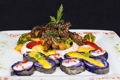 Pulpo asado a la parrilla, plato gastrónomo de Perú Servido con las patatas púrpuras (nativa) Imagen de archivo libre de regalías