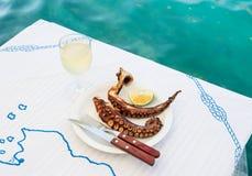 Pulpo asado a la parrilla y copa de vino blanca en una tabla en la costa de mar Fotos de archivo