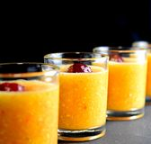 Pulpy orange drink with cherry in shot glasses stock images