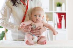 Pulsação do coração de exame do pediatra fêmea do bebê com estetoscópio Imagem de Stock Royalty Free