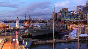 Pulsating city at harbor with navy ship by dusk Royalty Free Stock Photography