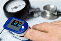Pulse oximeter. A pulse oximeter used to measure pulse rate and oxygen levels with Sphygmomanometer and medical stethoscope and ECG background royalty free stock photo