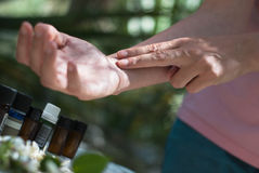 Pulse points, taking pulse, checking pulse. Woman checks pulse point, essential oils in the background with rose, neroli and jasmine flowers Stock Photos