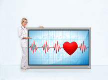 Pulse rate on tv screen. Woman doctor with stethoscope showing pulse rate on tv screen Royalty Free Stock Image