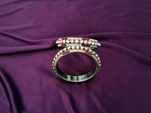 Pulseira indianas Bracelete com os diamantes no fundo violeta fotografia de stock