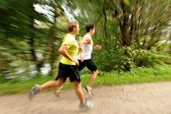 Fonctionnement de deux athlètes d'hommes/pulsant Photo stock