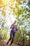 Pulser fonctionnant de femme de forme physique le long d'une forêt, d'un exercice et d'un fitne photos stock