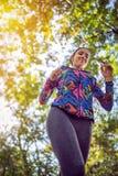Pulser fonctionnant de femme le long d'un conce de forêt, d'exercice et de forme physique images libres de droits