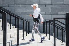 Pulser supérieur solennel de femme extérieur sur les étapes en pierre avec des balustrades Photos stock