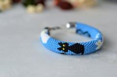 Pulsera azul con la imagen de gatos blancos y negros Foto de archivo libre de regalías