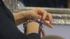 Pulsera azul de la joyería de la gema en su brazo Imagen de archivo