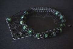 Pulsera con jade en un fondo negro fotos de archivo