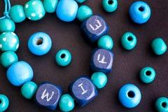 Pulsera con las gotas de madera azules con la ESPOSA de las letras en backg negro Imagen de archivo