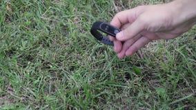 Pulsera de la aptitud El hombre encontró un reloj listo en la hierba El hallazgo Reloj listo en la hierba almacen de metraje de vídeo