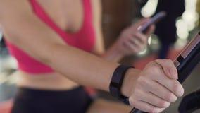 Pulsera de la aptitud en la mano de la mujer, bicicleta estática atlética del montar a caballo de la muchacha, primer almacen de metraje de vídeo