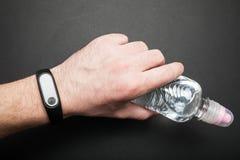 Pulsera de la aptitud en la mano de un hombre con una botella de agua imágenes de archivo libres de regalías
