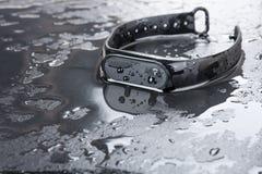 Pulsera de la aptitud en un fondo negro de la pizarra con descensos del agua Fotografía de archivo libre de regalías