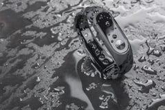Pulsera de la aptitud en un fondo negro de la pizarra con descensos del agua Foto de archivo libre de regalías