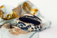 Pulsera del leopardo en la bufanda de seda fotografía de archivo