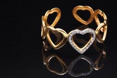 pulsera del oro con los corazones Imagenes de archivo