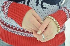 Pulsera en el primer de la mano del ` s de la muchacha Fondo del suéter del invierno Fotos de archivo libres de regalías