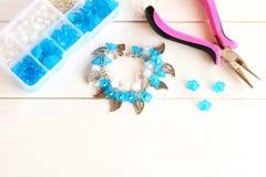 Pulsera hecha a mano con las flores, las gotas y los colgantes del metal Organizador con los accesorios para hacer la joyería Imagen de archivo libre de regalías