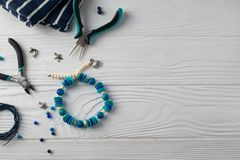 Pulsera hecha a mano de la turquesa, composición puesta plana de arriba con los alicates, gotas y herramientas imagen de archivo libre de regalías