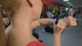Pulsera juguetona del perseguidor de la aptitud de la transferencia de la mujer antes del entrenamiento activo en gimnasio almacen de video