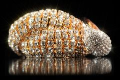 Pulsera y anillo brillantes del oro en fondo negro Imagenes de archivo
