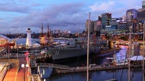 Pulserar staden på hamnen med marinskeppet vid skymning Royaltyfri Fotografi