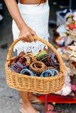 Pulseras coloridas de las artesanías nativas en la cesta Cesta que lleva de la mano de la mujer con por completo de pulseras hech Fotos de archivo