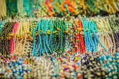 Pulseras, gotas y recuerdo coloridos de los collares para la venta en str Imagenes de archivo