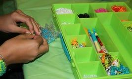 Pulseras que tejen adolescentes Imagen de archivo libre de regalías