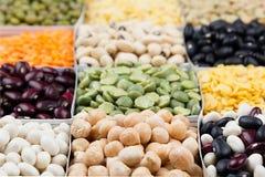 Pulsiert Lebensmittelhintergrund, Zusammenstellung - Hülsenfrucht, Gartenbohnen, Erbsen, Linsen in den quadratischen Makro Zellen Stockfotografie