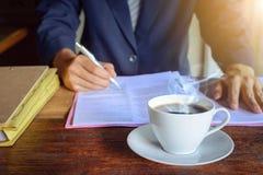 pulso de disparo e trabalho do copo de café na tabela Imagens de Stock Royalty Free
