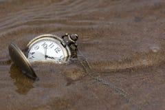 Pulso de disparo redondo com as mãos que encontram-se na areia molhada sob a água Fotos de Stock Royalty Free