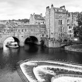 Pulteney Bridge in Bath. Somerset, UK. Black and white. The Pulteney Bridge Georgian architecture over the river Avon with weir and tour boat in Bath, Somerset Stock Photos