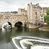Pulteney Bridge in Bath, Somerset, UK. The Pulteney Bridge Georgian architecture over the river Avon with wier and tour boat in Bath, Somerset, England. Designed Stock Photography
