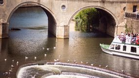 Pulteney Bridge and River Avon. Bath, England. 4th July, 2015:  The Weir and boat full of tourist in  River Avon,  Bath Somerset England UK Royalty Free Stock Photo