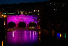 Pulteney bro exponerad i rosa färger på natten i badet, Somerset, UK royaltyfri foto