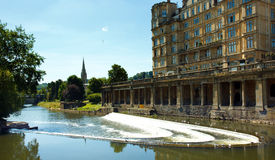 The Pulteney weir in Bath. The Pulteney Weir on the river Avon in Bath and the Empire Hotel now apartments for the elderly Royalty Free Stock Photo