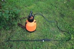 Pulvérisateur en plastique de jardin avec la pompe à main sur l'herbe Photographie stock