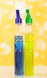 Pulvérisez l'agent de nettoyage de bouteilles sur le fond jaune abstrait photos stock