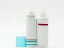Pulvérisez la bouteille avec le chapeau bleu ouvert et la bouteille de pompe de soins de la peau sur le fond blanc, masquent le l images libres de droits